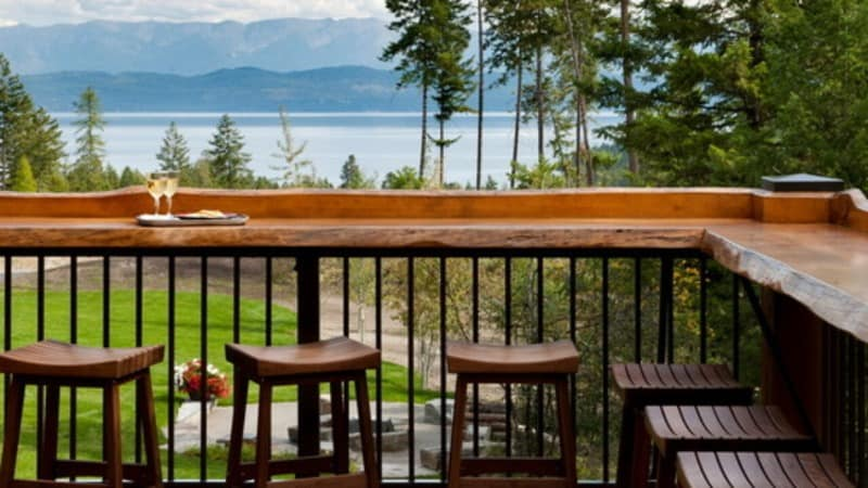 Built-in outdoor bar decks with a view of water past trees