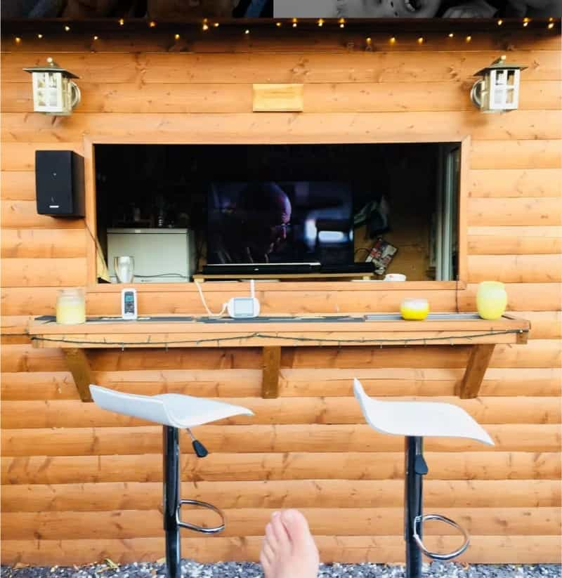 Log cabin bar with breaking bad playing through a hole-in-the-wall