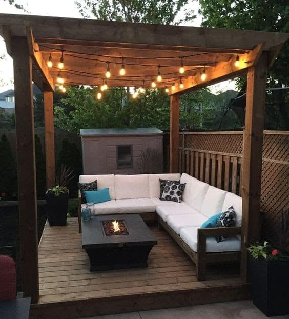 A free-standing pergola in the corner of a garden