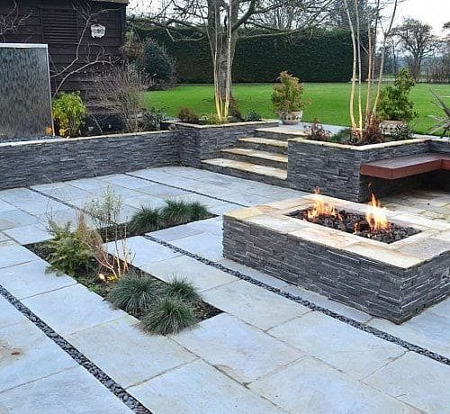 A contemporary courtyard featuring bright sandstone and a fire pit