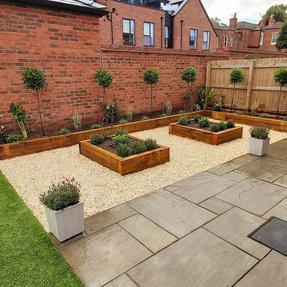 A neat backyard with a brown porcelain coloured deck and some pebbles for the raised garden