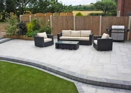 A bright sandstone paving outdoor lounge with grill and a rattan garden furniture set