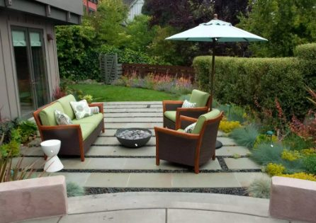 Small patio designed with Bluestone bands and black pebbles