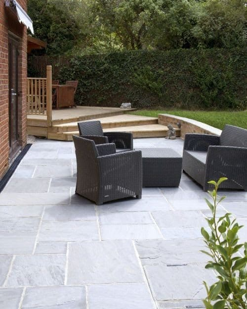 Backyard set-up with a rattan garden furniture set in grey colour, matching the silver grey sandstone
