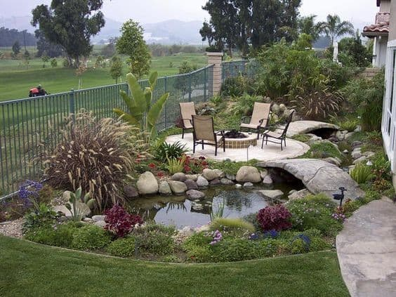 A mini bridge which leads to a garden retreat with outdoor furniture and a mini pond