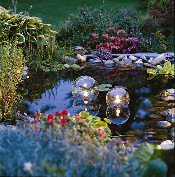 A garden pond with floating eclectic lighting