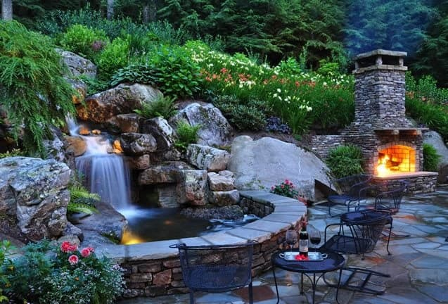 A waterfall, a brick oven on the side that can double as a fireplace, and some garden tables and chairs around the pond