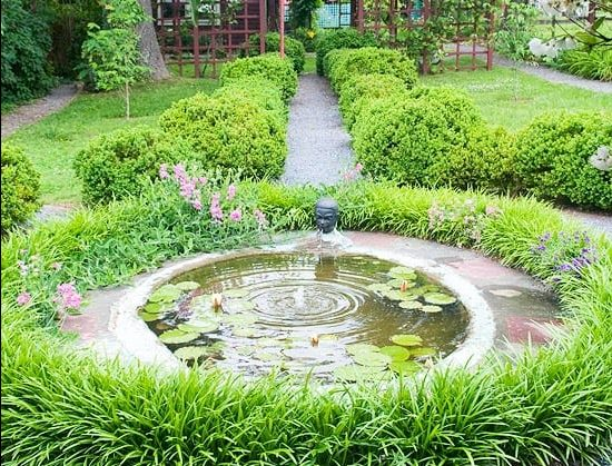 Mini round-shaped pond within a circular lawn border