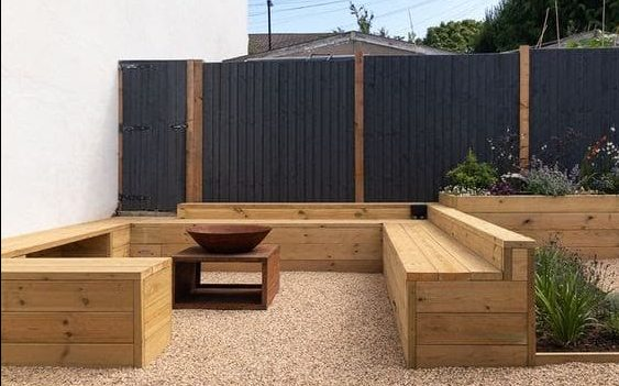 Small garden featuring wooden benches and a fire pit with black fencing