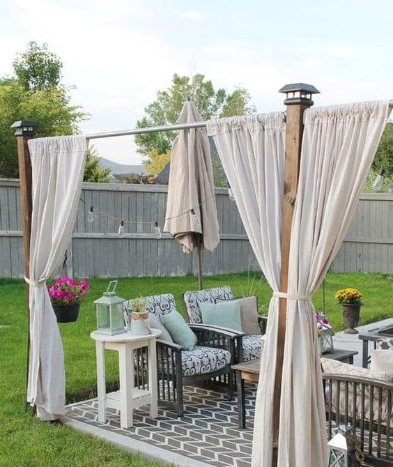 Separated outdoor dining with curtains and patio umbrella