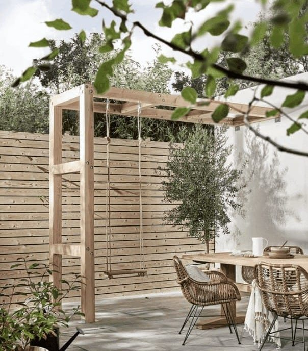 Light wood garden fence, alongside pale tones of grey and white outdoor fixtures