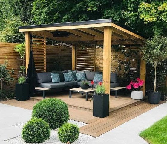 A modern decked area with a gazebo and wooden fence