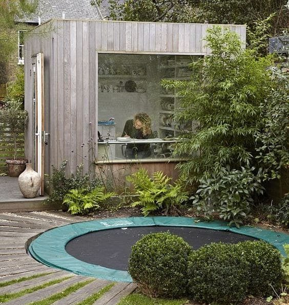A small garden office with a large window to keep an eye on the children while playing outdoors