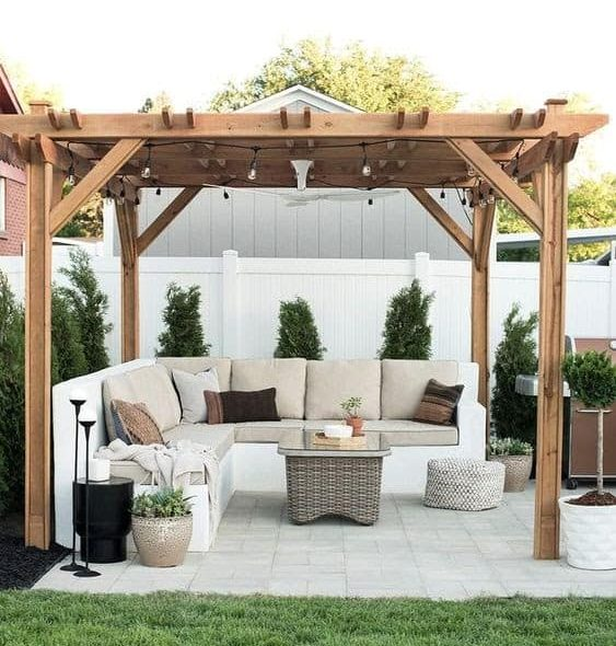 A garden pergola with a wooden roof and L-shaped corner sofa set