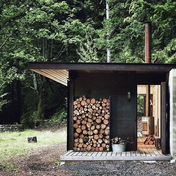 A small garden office set-up made out of shipping container, with pile of logs on the side