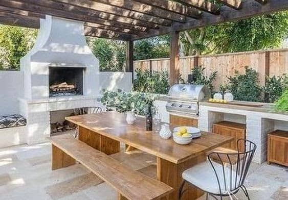 A Mediterranean-inspired outdoor dining set-up with fully furnished outdoor kitchen