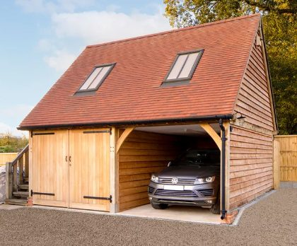 A wooden garage featuring an oak-frame structure, with a room above