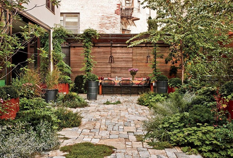 Tucked-away outdoor dining space set against at the back wall of a lush garden