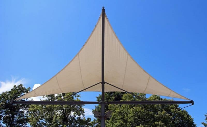 sun shade sail in a triangle against trees and a blue sky