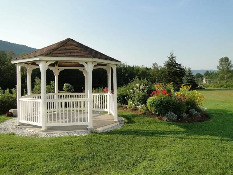 white gazebo bandstand on gravel patch by a lawn with bushes