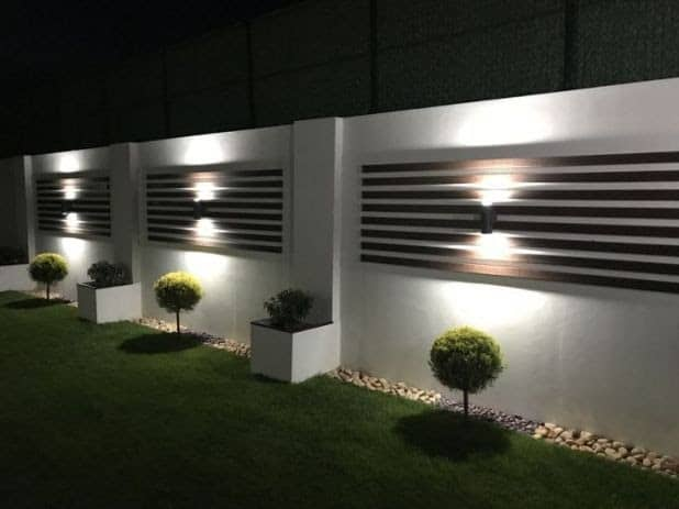 Modern backyard lighting on a white wall with wooden cladding