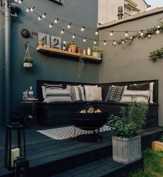 A comfy lounge on a deck, complete with lights and a fire pit