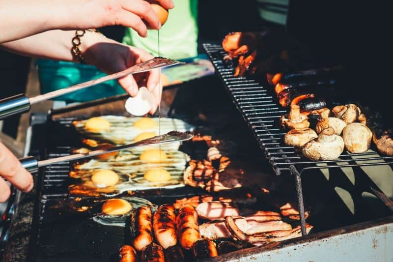 Sausages, mushrooms, and eggs being grilled