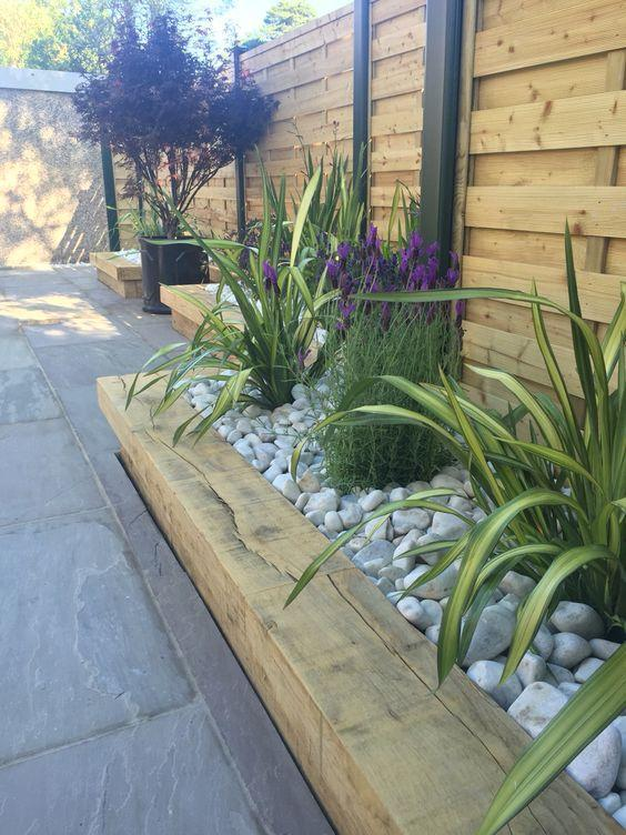 Pebbled borders with plants against a fence