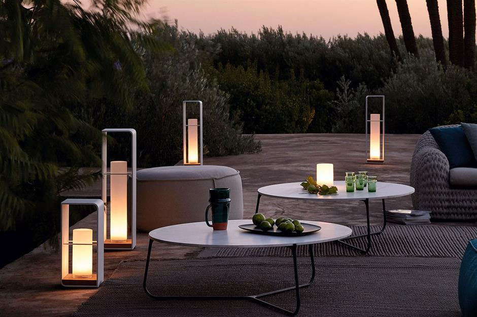 modern shape lighting with round white tables at dusk