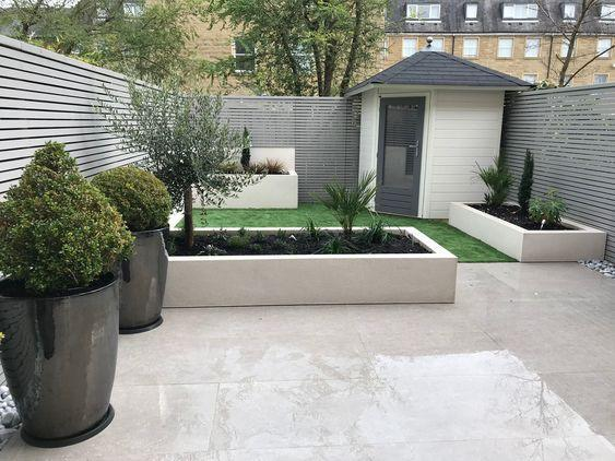 wet patio with large potted plants and corner shed in modern garden