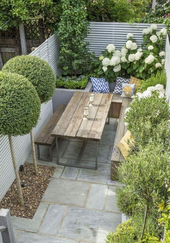 Small Garden with wood table and pruned trees