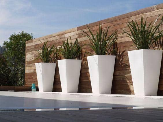 modern white plant pots against a water feature
