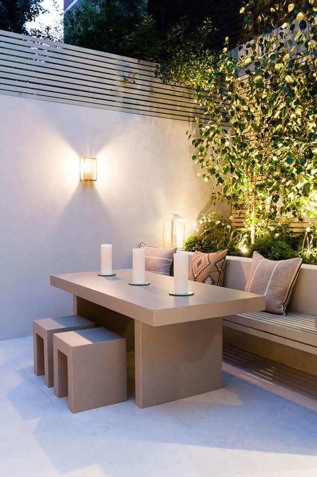 small garden lighting around beige marble table with cube chairs