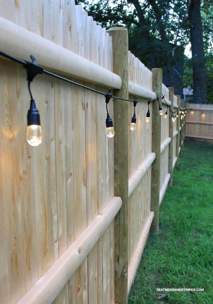 backyard lights hanging from a fence