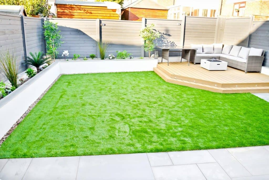 Open minimalist garden with large green lawn and raised decking