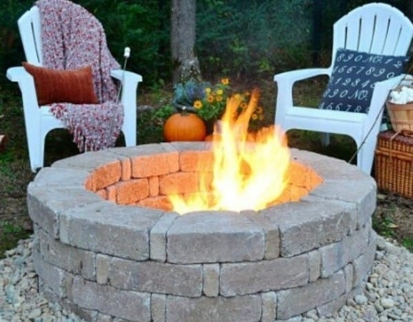 round stone fire pit with chairs