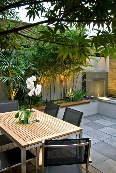 minimalist garden on tiled patio with table and chairs