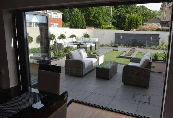 elegant modern garden with wide-open doors and patio furniture