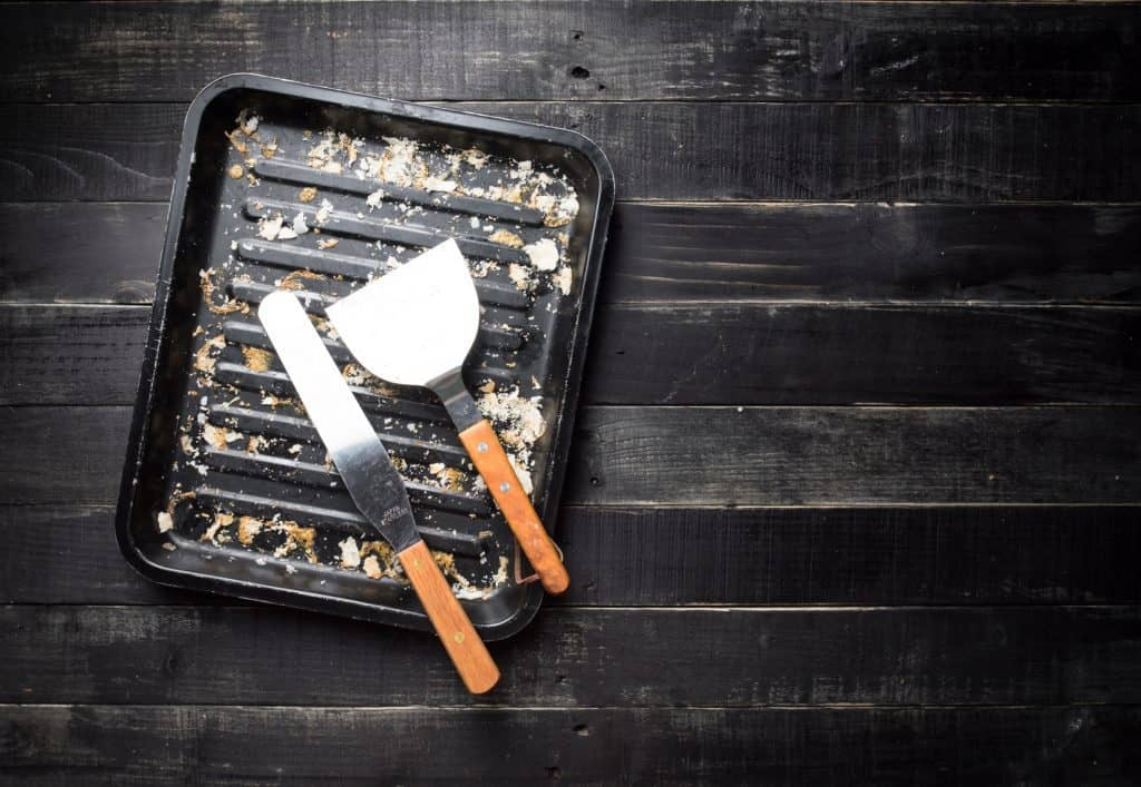Metal baking tray and kitchen spatula with bread crumbs on dark wooden background,top view