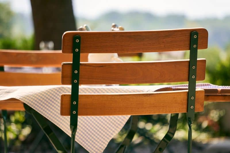 A wooden bistro chair with steel framework