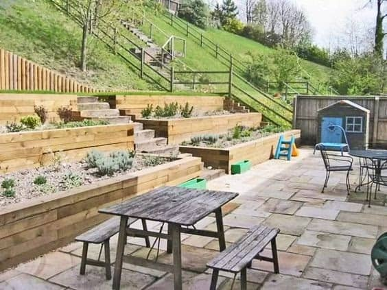 A sloped hill transformed into a cosy backyard by using tiered wooden planters and a picnic area