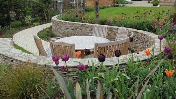 A round retaining wall into the hillside, creating a perfect space for outdoor dining
