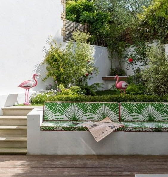 A retaining wall with added cushions, serving as a comfy sofa