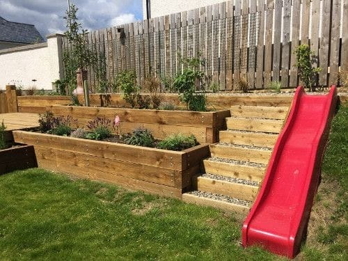A red slide beside the wooden steps outdoors