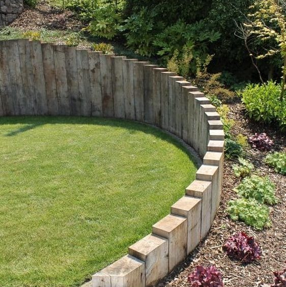 A levelled garden with a strong retaining wall on a messy sloped hill