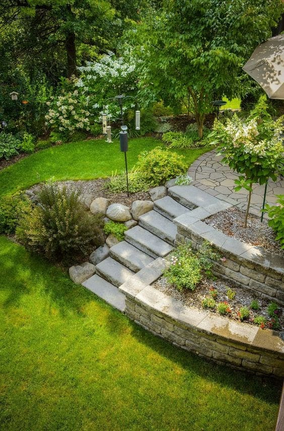 A garden with beautiful stone steps and tiered raised beds