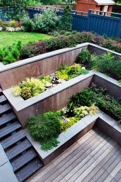 Steep sloped garden with stairs and tiered planters