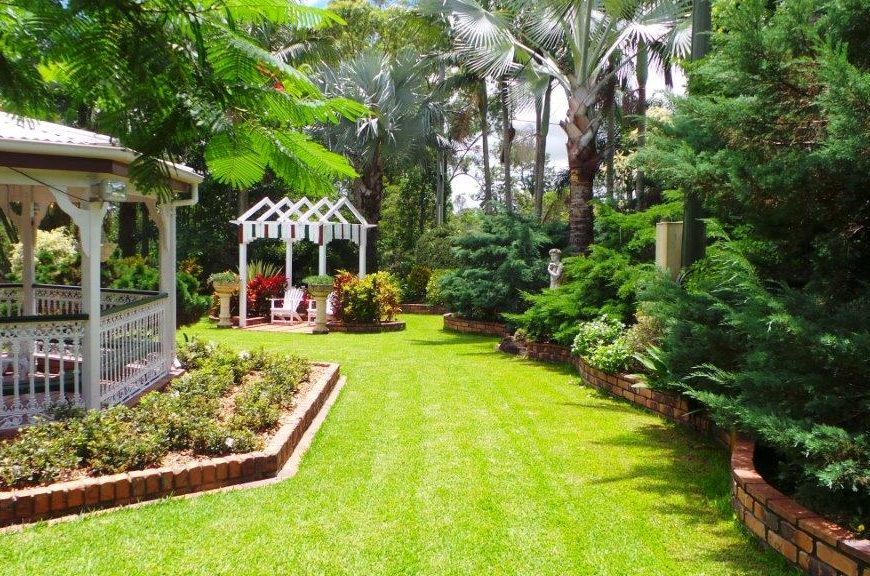 Open garden with a tidy lawn and classic raised flower beds on the garden border