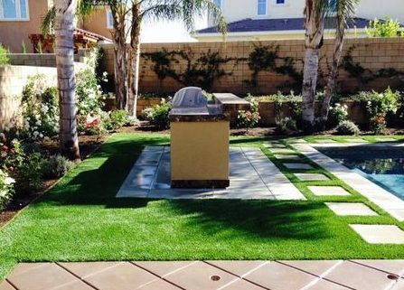Grill, table and grass creating the perfect outdoor hangout spot