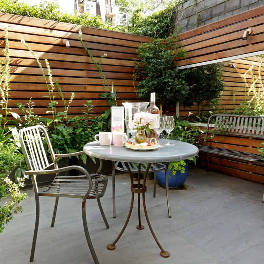 A small table set surrounded by lush green plants and trees